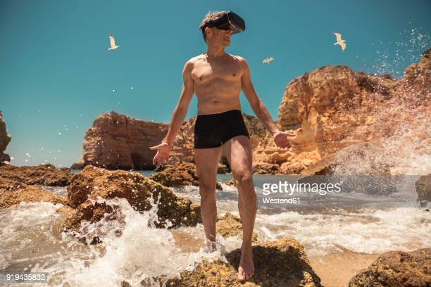 Mature man wearing VR glasses between rocks on beach