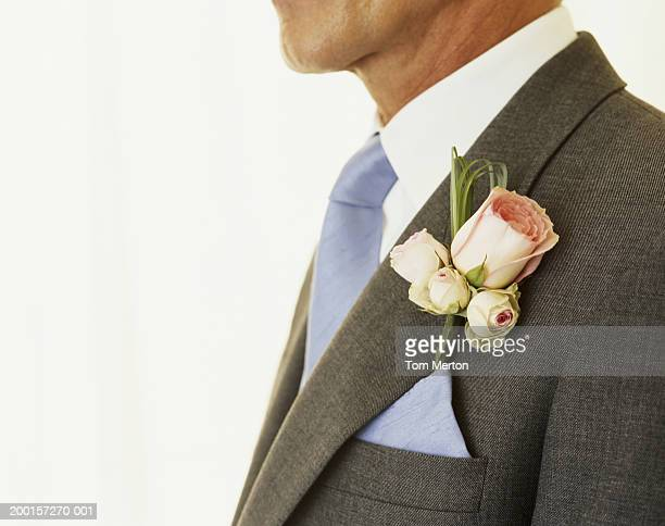 Mature man wearing wedding buttonhole, mid section