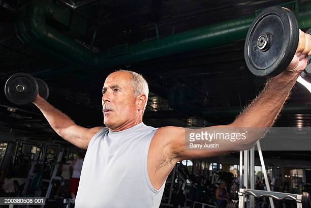 mature man weight training in gym, low angle view - receding hairline stock pictures, royalty-free photos & images