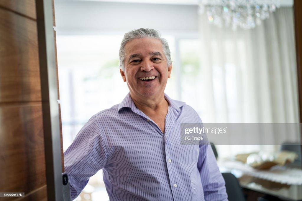 Mature Man Welcoming Home Opening His Front Door : Stock Photo
