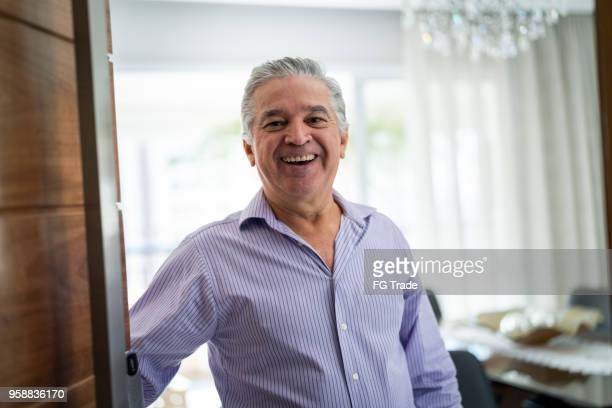 mature man welcoming home opening his front door - porta imagens e fotografias de stock