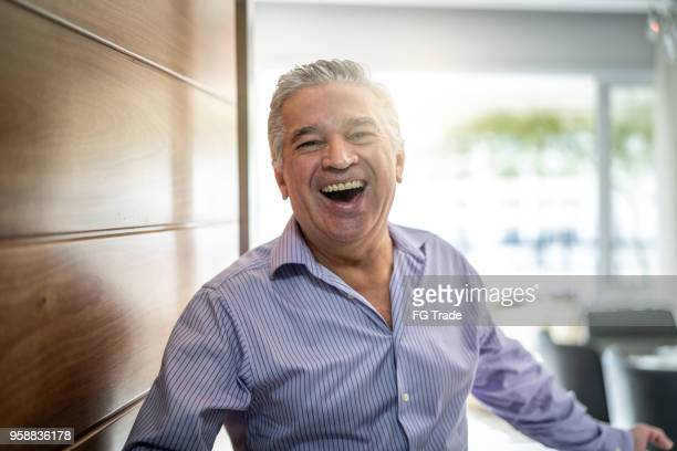 mature man welcoming home opening his front door - welcoming guests stock photos and pictures