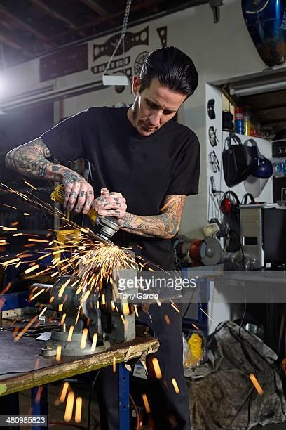 mature man welding parts in motorcycle repair workshop - kunsthandwerkliches erzeugnis stock-fotos und bilder