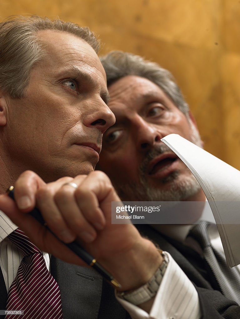 Mature man whispering to colleague in pew, close-up : Stock Photo