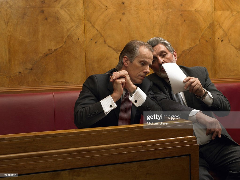 Mature man whispering to colleague in pew : Stock Photo