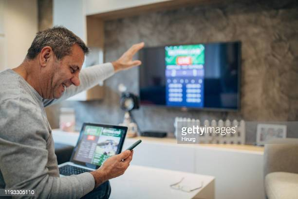 mature man wins the online bet - the championship football league stock pictures, royalty-free photos & images