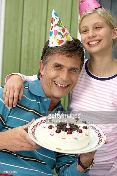 Mature Man With A Birthday Cake In His Hand Next To Blond Daughter Both