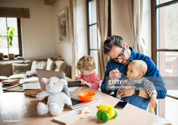 mature man with a boy and girl working at home office, using laptop and feeding his toddler children. - feeding stock pictures, royalty-free photos & images