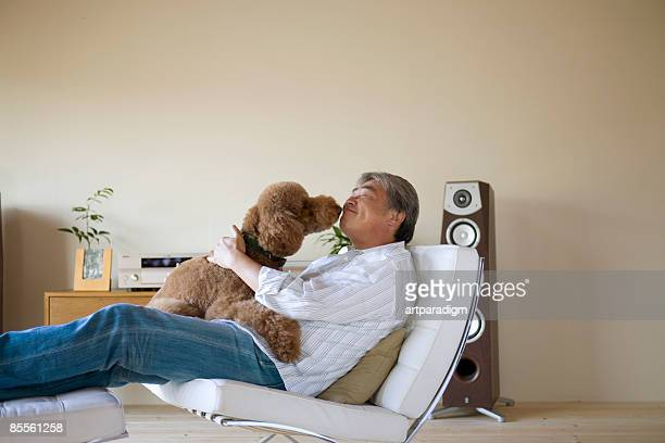 a mature man with a dog - reclining chair stock photos and pictures