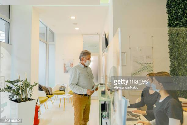 mature man with a protective face mask arriving at the medical clinic - medical receptionist uniforms stock pictures, royalty-free photos & images