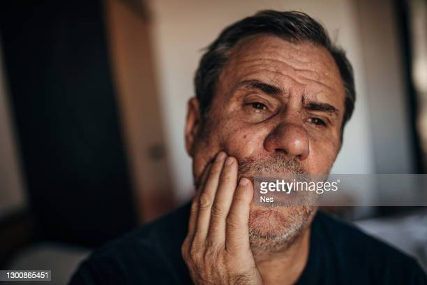a mature man with a toothache - injured stock pictures, royalty-free photos & images