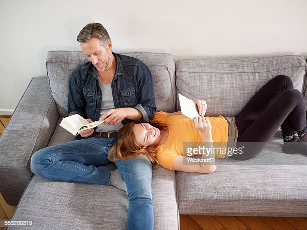 Mature man with adult daughter reading on sofa