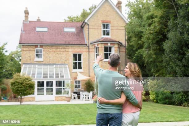 Reifer Mann mit Arm um Frau und zeigt in Richtung ihres Hauses
