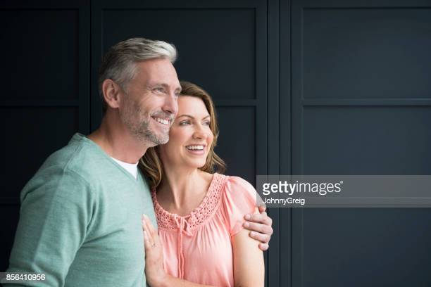 Mature man with arm around woman in front of dark blue wood panelling