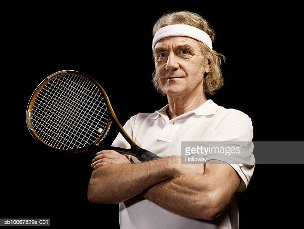 Mature man with arms crossed holding tennis racket on black background