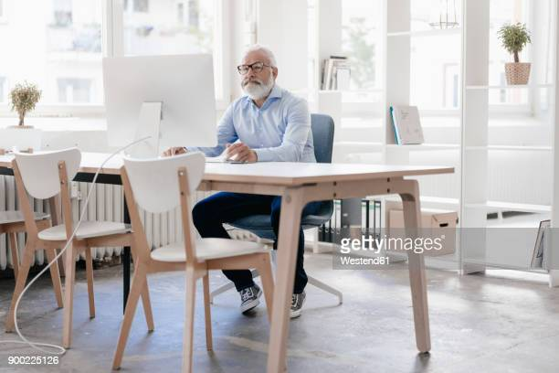 Mature man with beard and glasses working at desk