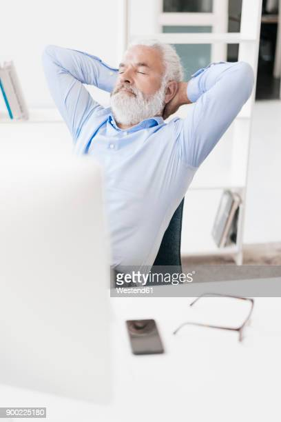 Mature man with beard relaxing at desk