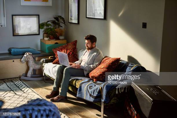 mature man with beard working from home on laptop - sofa stock pictures, royalty-free photos & images