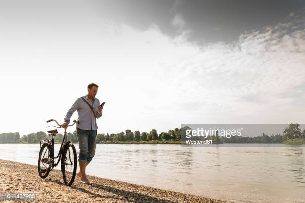 mature man with bike using smartphone at rhine riverbank - rhine river stock pictures, royalty-free photos & images