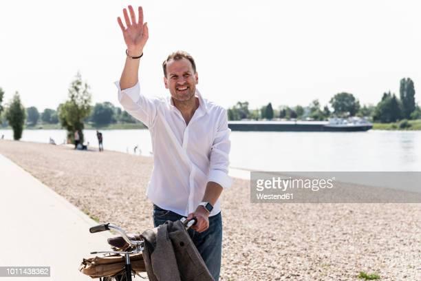 mature man with bike waving at rhine riverbank - zwaaien gebaren stockfoto's en -beelden