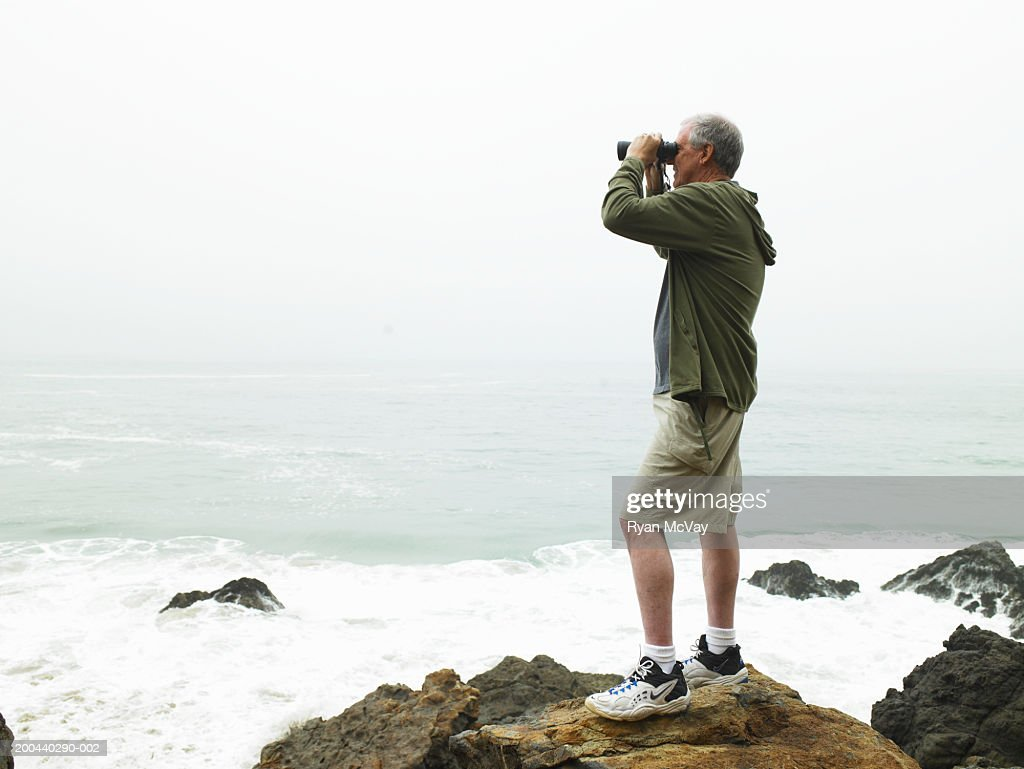 mature man with binoculars standing on rocks on beach ストックフォト