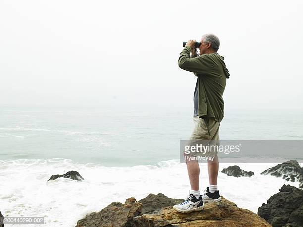 Mature man with binoculars standing on rocks on beach