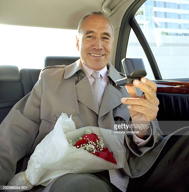 Mature man with bouquet of roses and jewelry box in back seat of car