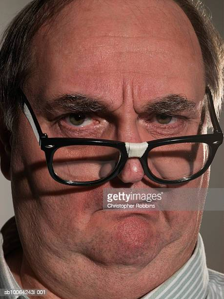 mature man with broken glasses, portrait, close-up - ugly bald man stock photos and pictures