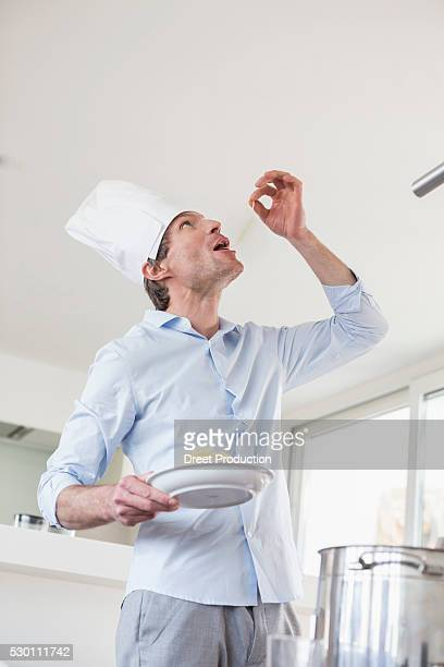 Mature man with chef's hat eating spaghetti
