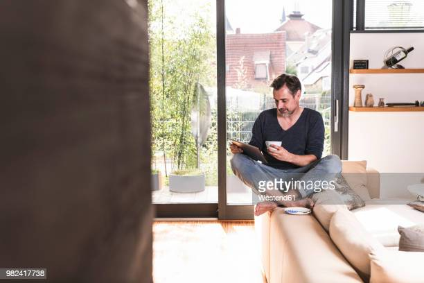 Mature man with cup of coffee sitting on backrest of couch using tablet