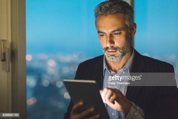 Mature man with digital tablet in the evening