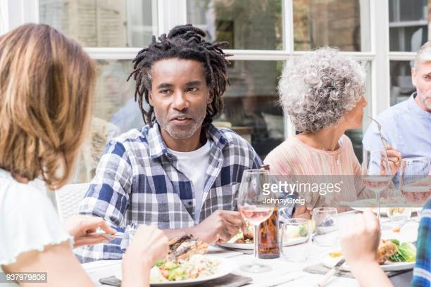 Mature man with dreadlocks talking to female friend at garden party