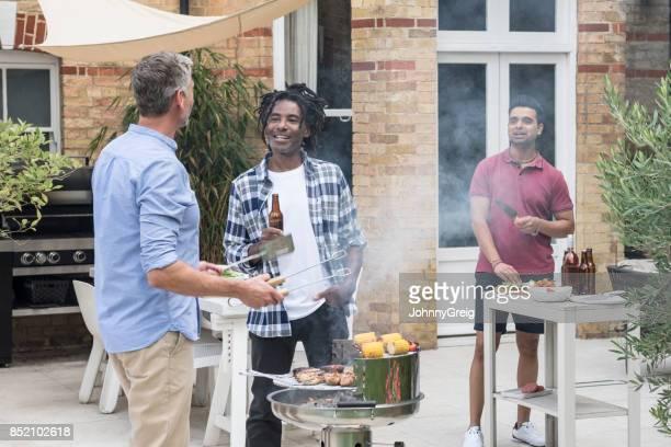 Mature man with dreadlocks talking to friend doing bbq