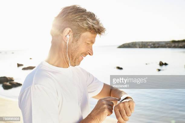 Mature man with earphone checking his smartwatch after yogging on the beach