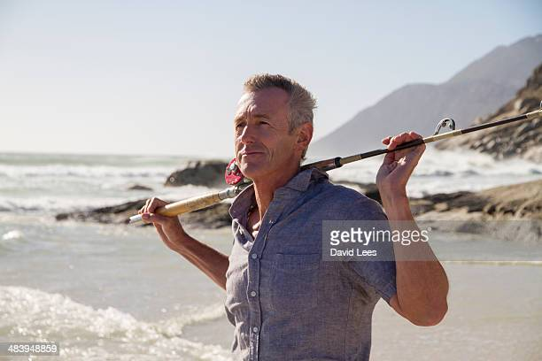 Mature man with fishing rod on beach