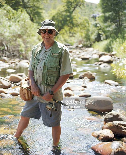 Mature man with fishing tackle in stream, smiling, portrait