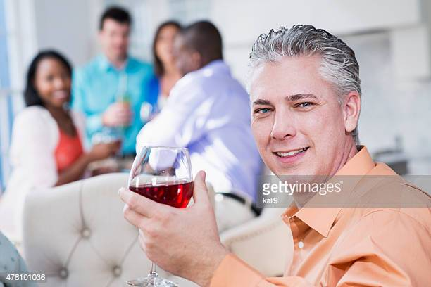 Mature man with glass of red wine at party
