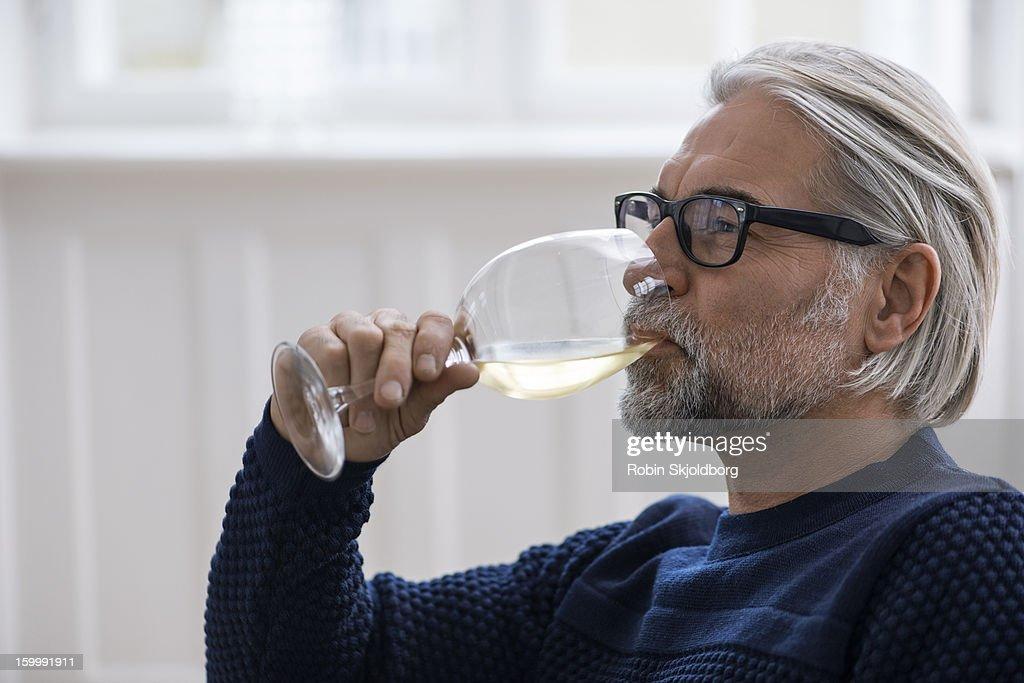Mature man with glasses drinking white wine : Stock Photo