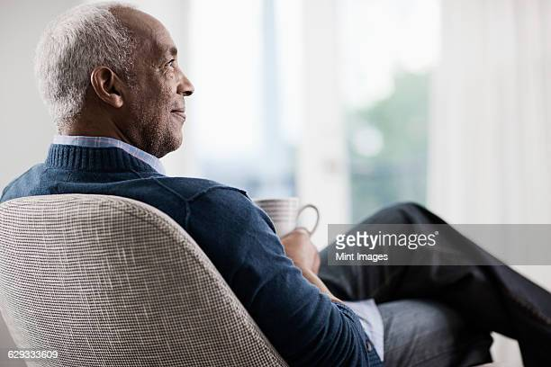 A mature man with grey hair leaning back in a chair, relaxing with a cup of tea or coffee.