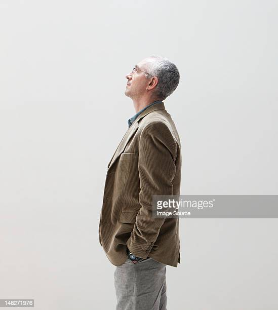 mature man with hands in pocket looking up, studio shot - dreiviertelansicht stock-fotos und bilder