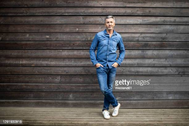 mature man with hands in pockets standing against wooden wall - mains dans les poches photos et images de collection