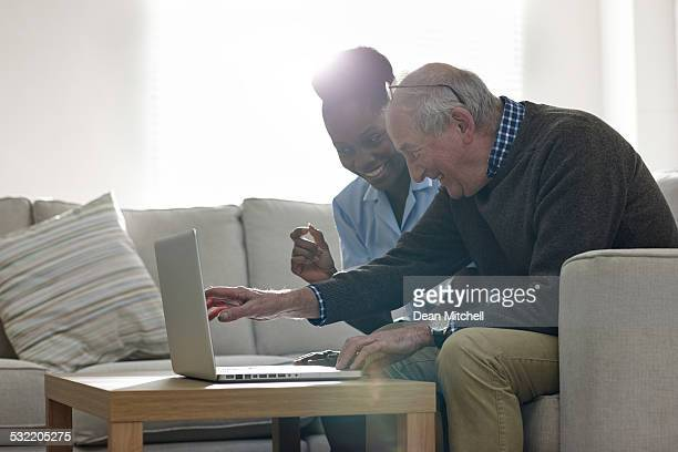 mature man with his nurse looking at the laptop - social services stock photos and pictures