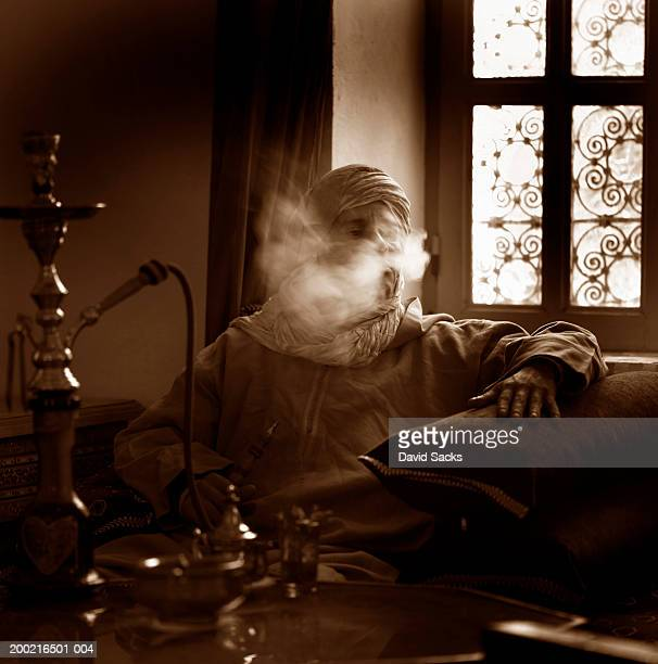 mature man with hookah pipe blowing out smoke (b&w) - 水キセル ストックフォトと画像