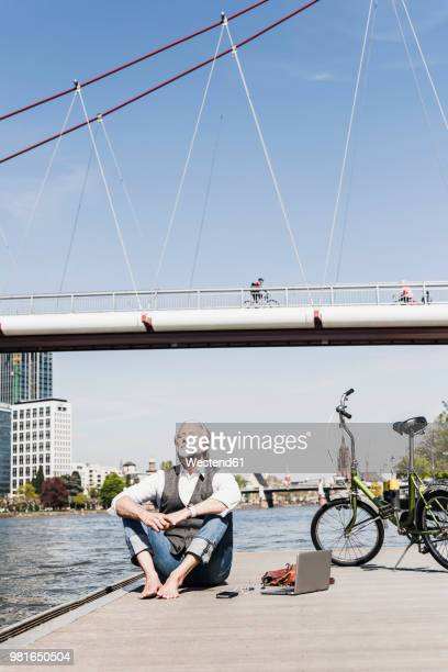 mature man with laptop and bicycle sitting at the riverside in the city - hesse duitsland stockfoto's en -beelden