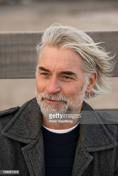 mature man with long grey hair smiling - robin skjoldborg stock pictures, royalty-free photos & images