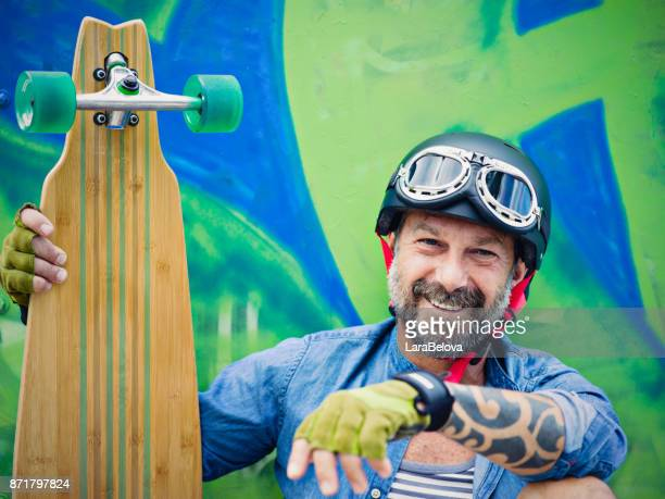 Mature man with longboard, graffiti on background