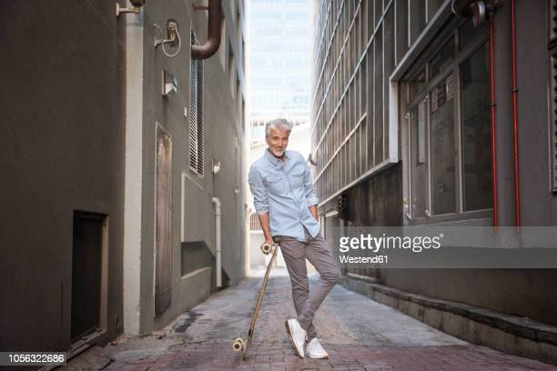 mature man with longboard in an alley - 気が若い ストックフォトと画像