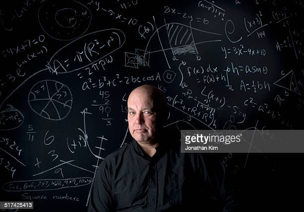 Mature man with math problems on chalkboard
