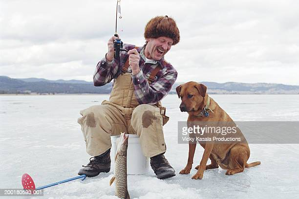 Mature man with mixed-breed dog ice fishing on frozen lake