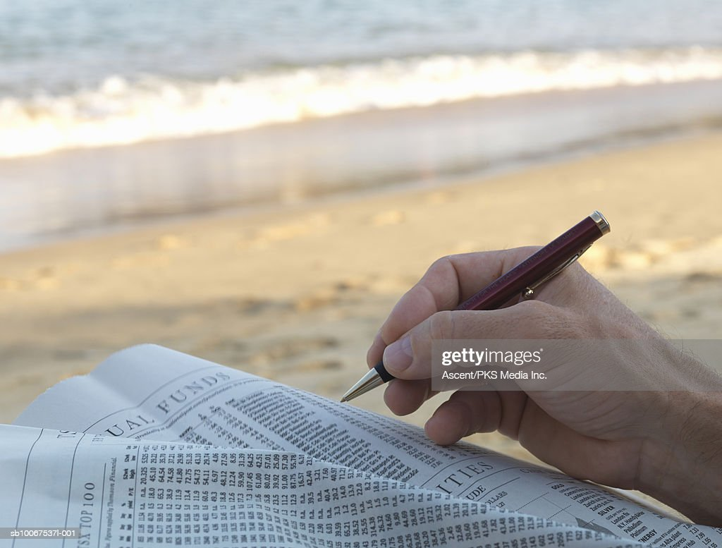 Mature man with newspaper at beach : Stock Photo